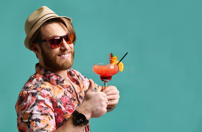 Młody człowiek up pije czerwonego margarita koktajlu napoju soku szczęśliwą patrzeje kamerę nad błękitem w kapeluszowym przedstaw obraz stock