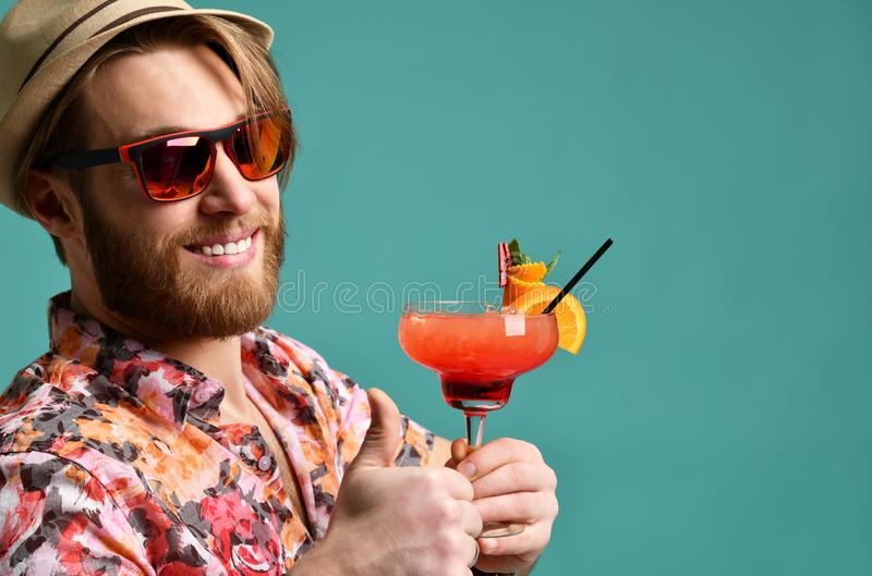 Młody człowiek up pije czerwonego margarita koktajlu napoju soku szczęśliwą patrzeje kamerę nad błękitem w kapeluszowym przedstaw zdjęcia stock