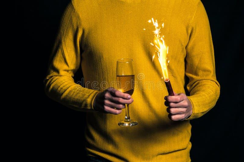 Młody człowiek w żółtym puloweru chwyta szampanie i błyskotaniu obrazy royalty free