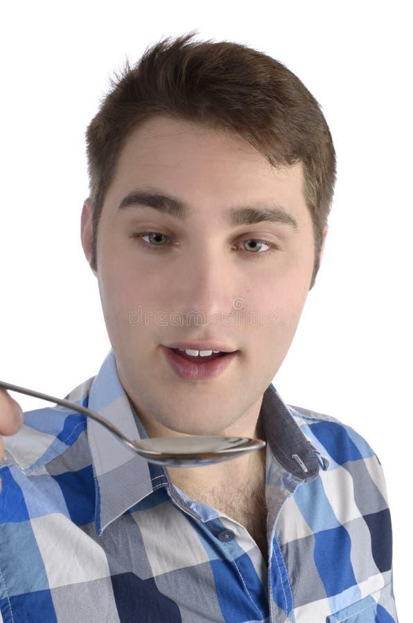 Młody człowiek w błękitnej koszula wącha łyżkę zdjęcia stock