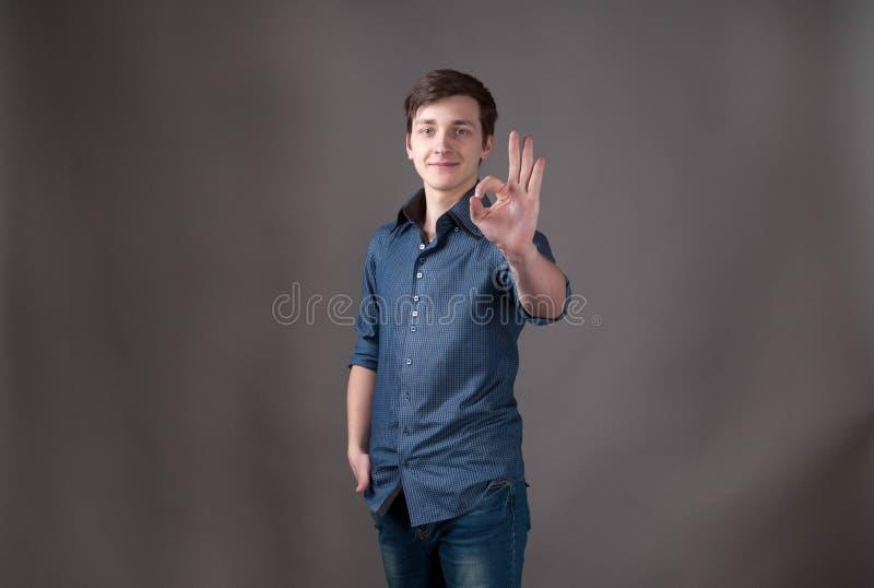 młody człowiek w błękitnej patrzeje kamerze i pokazywać ok znaka zdjęcie stock