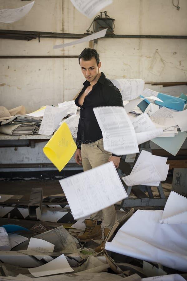 Młody człowiek w bardzo upaćkanym biurze z dokumentów latać obrazy stock