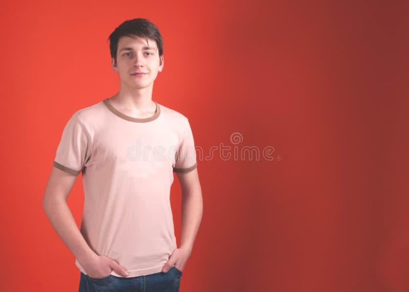 Młody człowiek w beżowej t koszulowej pozycji z rękami w kieszeniach i patrzeć kamerę na koralowym koloru tle obraz stock