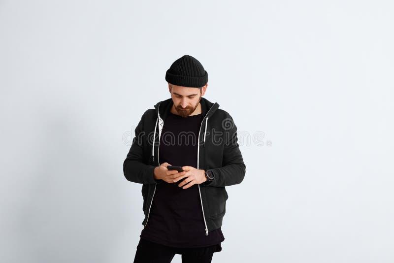 Młody człowiek w czarny patrzeć na jego smartphone obraz stock
