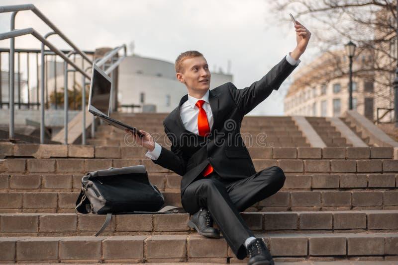Młody człowiek w czarnym kostiumu czerwonym krawacie i bierze selfie na smartphone Mężczyzna z laptopem siedzi na krokach w mieśc zdjęcie royalty free