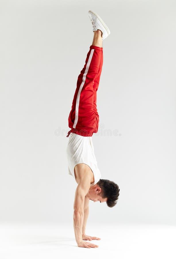 Młody człowiek w czerwonych sweatpants robi handstand na rękach na białym tle obraz royalty free