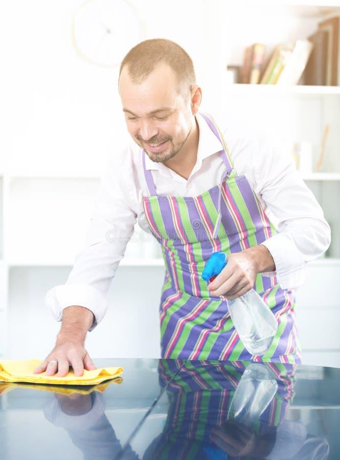 Młody człowiek w fartucha cleaning stole fotografia royalty free