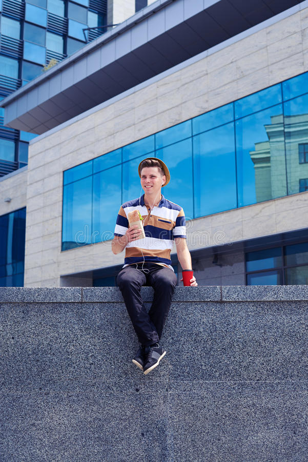 Młody człowiek w hełmofonach ma lunch podczas gdy siedzący na kamiennej ścianie obraz stock