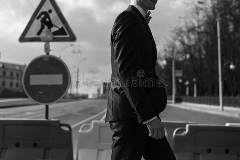 Młody człowiek w kostiumu chodzi wzdłuż zwyczajnego skrzyżowania Na drogowym znaku jest w budowie zdjęcie stock