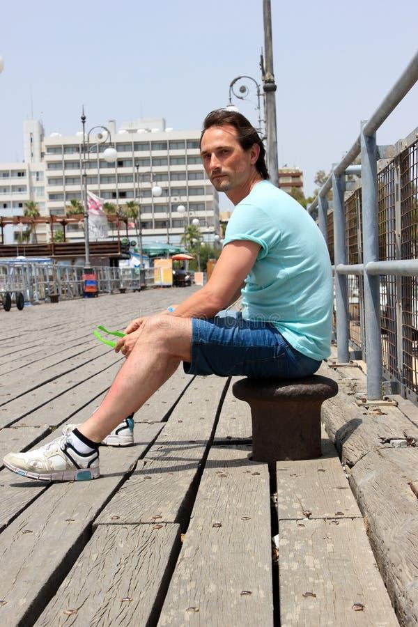 Młody człowiek w koszulki obsiadaniu na cumownicie przy drewnianym molem z barierą w marina blisko hotel obraz royalty free
