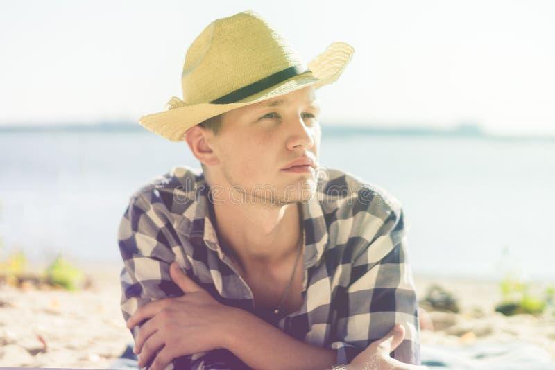 Młody człowiek w lata kapeluszowym lying on the beach na morze plaży zakończenie w górę portretów zdjęcia stock