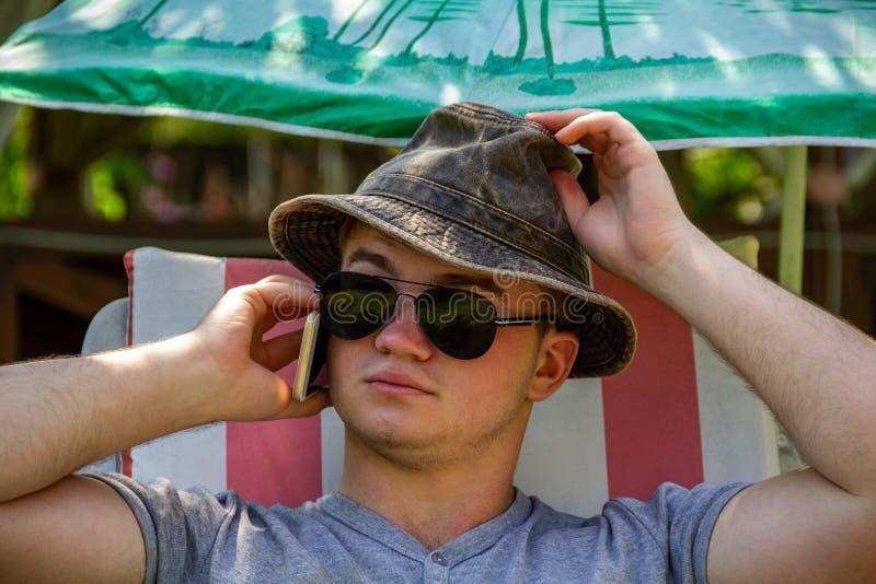 Młody człowiek w lecie w kapeluszu i okularach przeciwsłonecznych, na słońca lounger w jasnej pogodnej pogodzie wśród summerhouse obrazy stock
