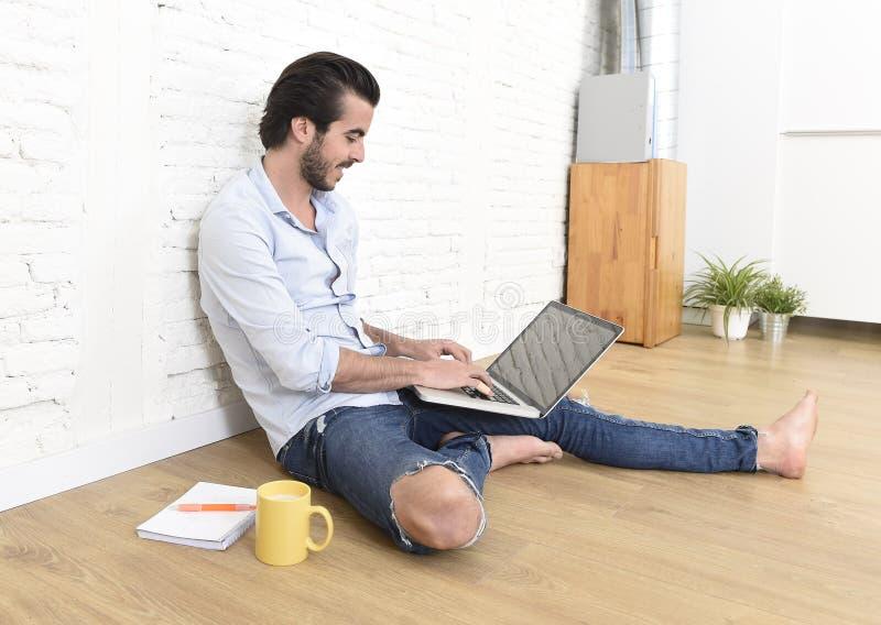 Młody człowiek w modnisia przypadkowego stylu spojrzenia nowożytnym obsiadaniu na żywego pokoju domu podłogowym działaniu na lapt fotografia royalty free