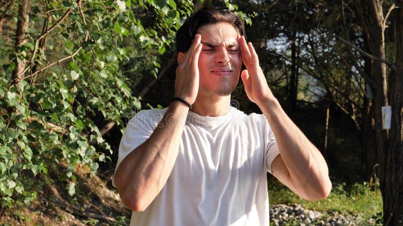Młody człowiek w natury cierpieniu od migreny zdjęcia stock