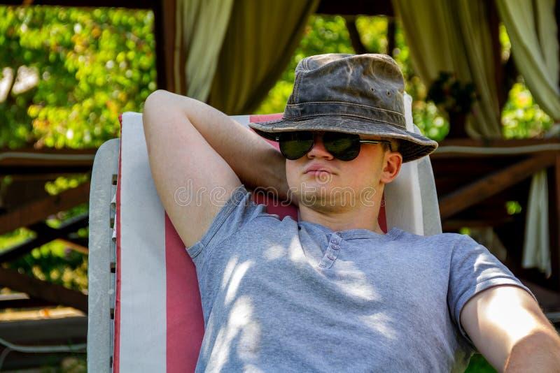 Młody człowiek w okularach przeciwsłonecznych i kapeluszu na holu krześle w jasnej pogodnej pogodzie, odpoczynkowy i relaksujący  obrazy stock