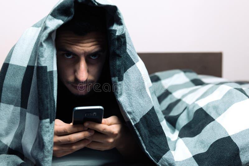 Młody człowiek w piżamach używać telefon komórkowego Konceptualna fotografia o ogólnospołecznym networking zdjęcia royalty free