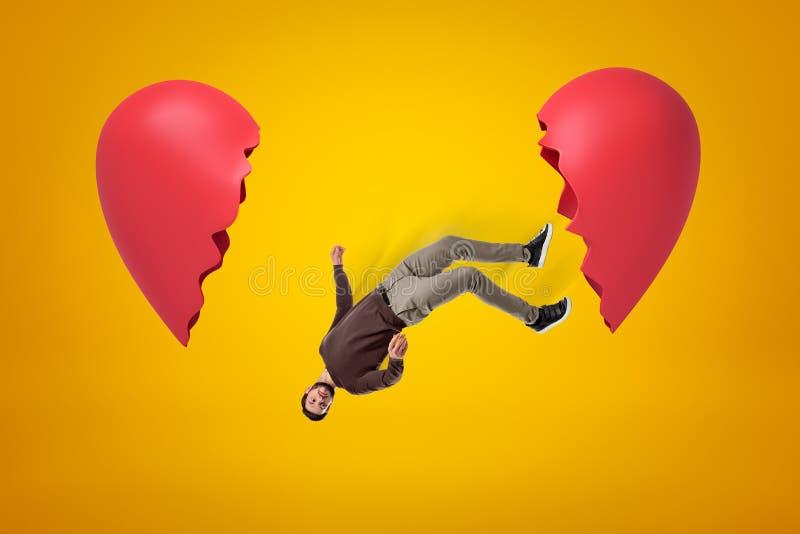 Młody człowiek w przypadkowych ubraniach spada między dwa złamane serce kawałkami na żółtym tle ilustracji
