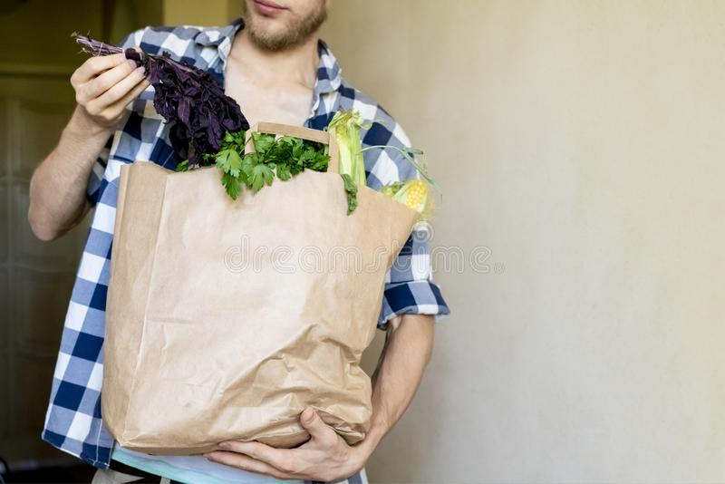 Młody człowiek w przypadkowym przychodził do domu od sklepu spożywczego i kupował niektóre świeżego sklep spożywczego w papierowe obraz stock