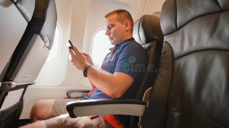 Młody człowiek w samolocie przed lotem komunikuje na telefonie komórkowym zdjęcia stock