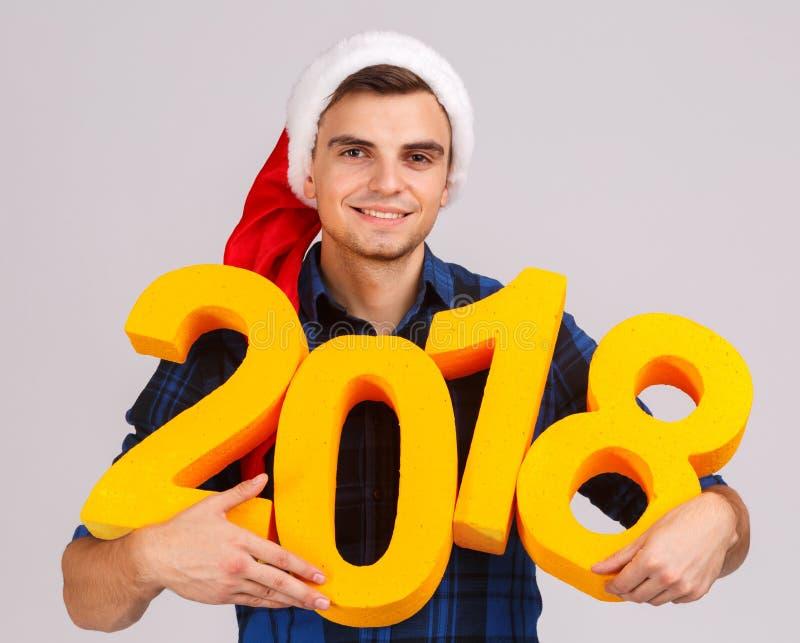 Młody człowiek w Santa ` s kapeluszu z złoto postaciami w 2018 w jego ręki obraz royalty free