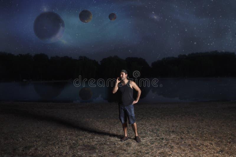 Młody człowiek w skrótach i nakrętce, przy nocą opowiada na telefonie komórkowym na brzeg rezerwuar przeciw tłu abstrakt fotografia stock