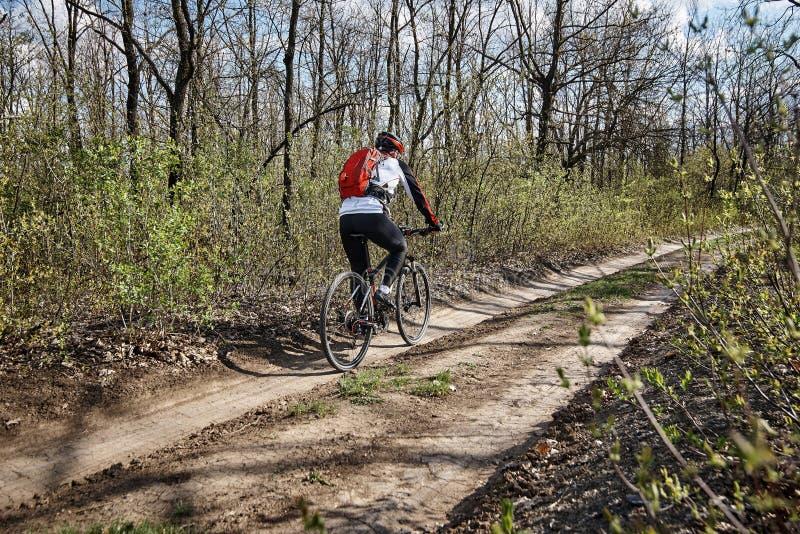Młody człowiek w sportach odziewa przejażdżki bicykl zdjęcie stock