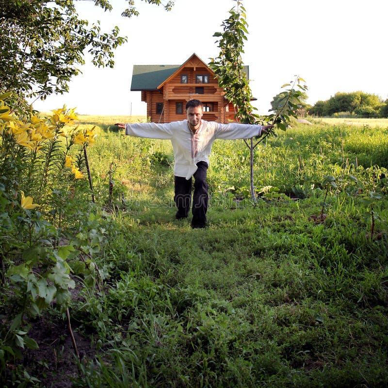 młody człowiek w upiększonych koszula pozach na kamerze wśród zielonych rośliien zdjęcia stock