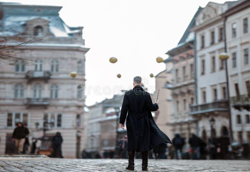Młody człowiek w wizerunku czarny magik chodzi na ulicie z magiczną różdżką obraz stock