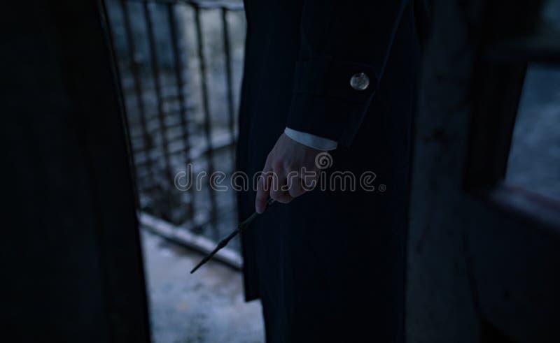 Młody człowiek w wizerunku czarny magik z magiczną różdżką w jego ręce zdjęcie stock