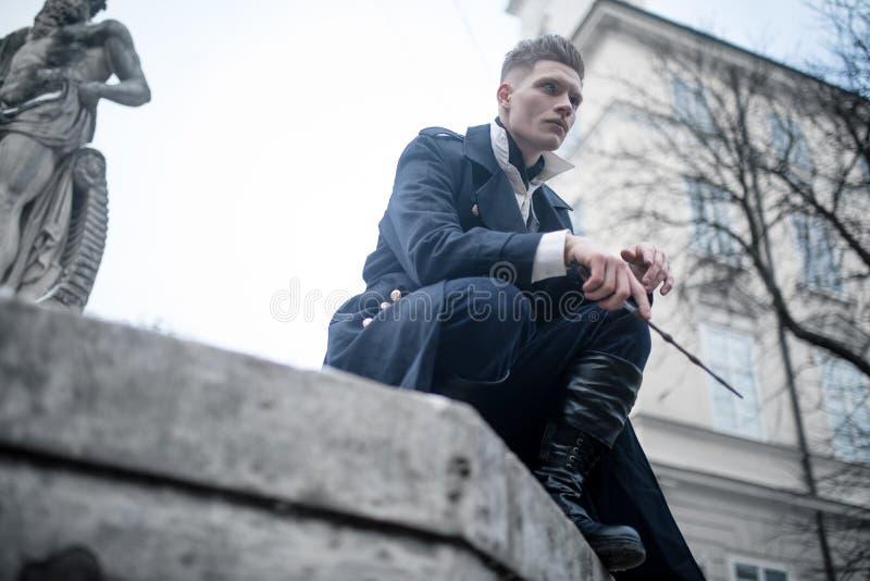 Młody człowiek w wizerunku czarny magik z magiczną różdżką na ulicie zdjęcie stock