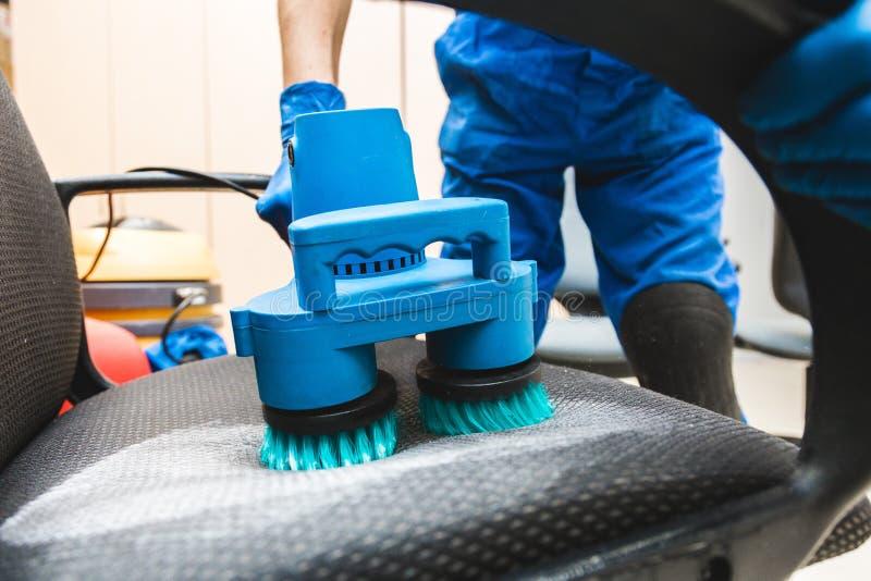 Młody człowiek w workwear i gumy rękawiczkach czyści biurowego krzesła z fachowym wyposażeniem fotografia stock
