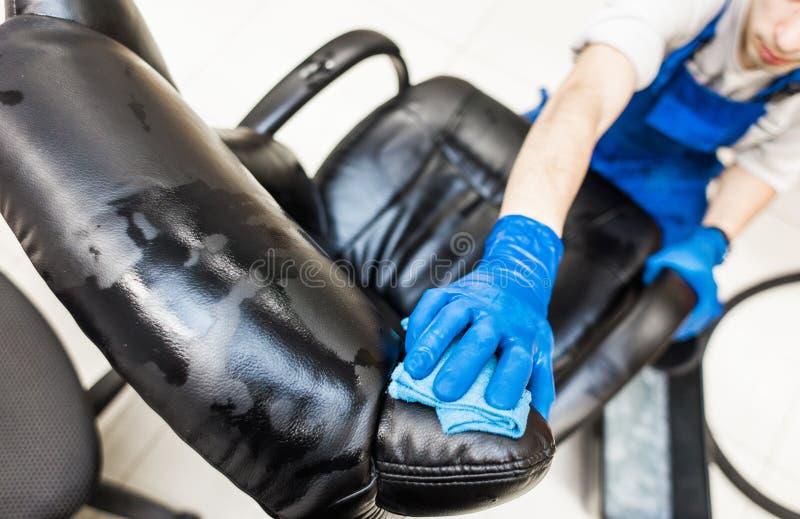 Młody człowiek w workwear i gumy rękawiczkach czyści biurowego krzesła z fachowym wyposażeniem zdjęcie stock