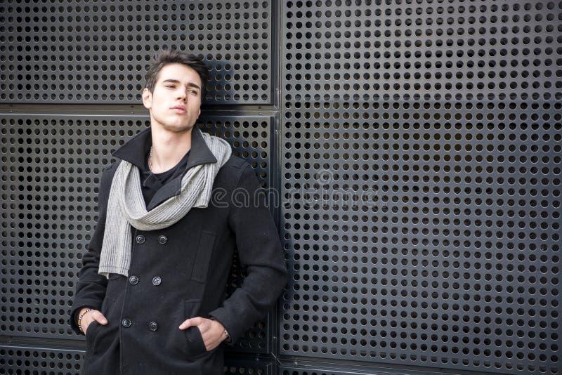Młody Człowiek w zima stroju Opiera na metal ścianie zdjęcia royalty free