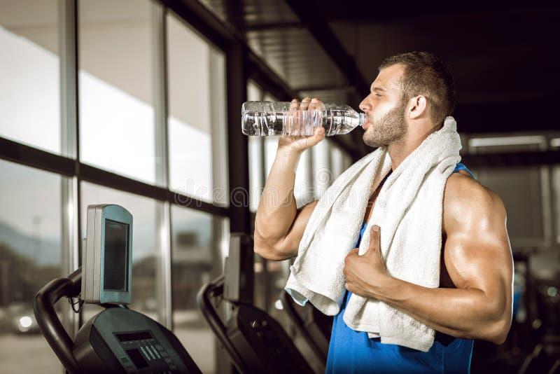Młody człowiek woda pitna w gym obrazy stock