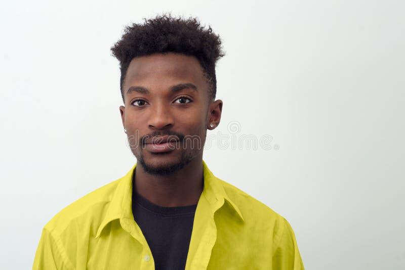 Młody człowiek wokoło dwadzieścia jest ubranym żółtej koszula na białym tle zdjęcie royalty free
