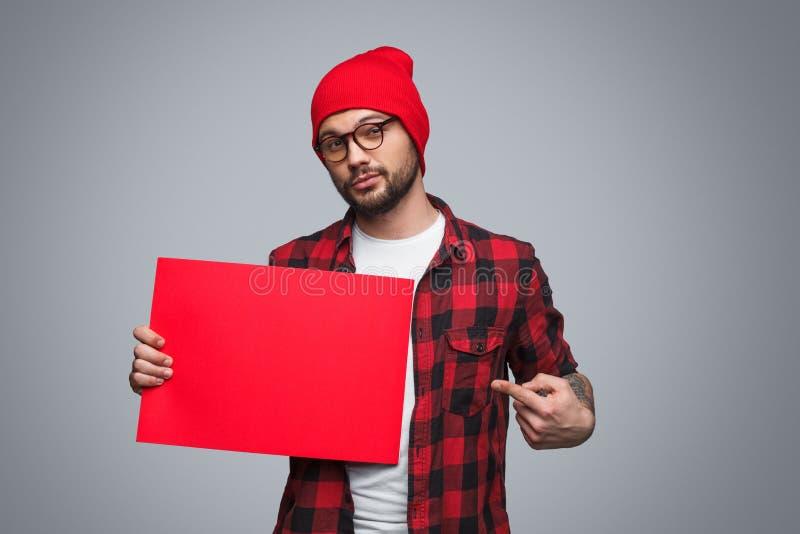 Młody człowiek wskazuje przy czerwonym plakatem obraz stock