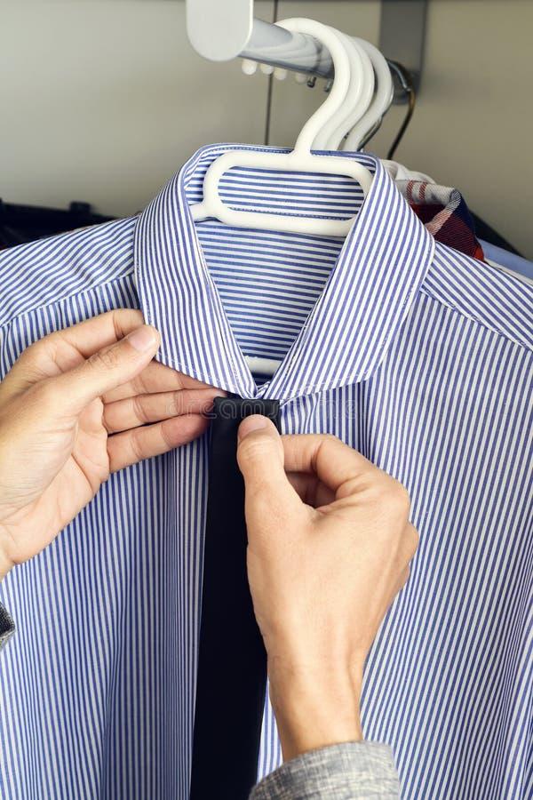 Młody człowiek wybiera krawat i koszula od szafy obrazy stock