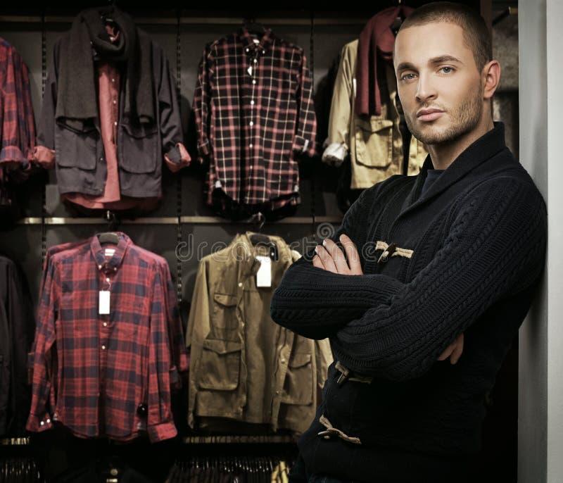 Młody człowiek wybiera odzieżowego w sklepie obraz royalty free