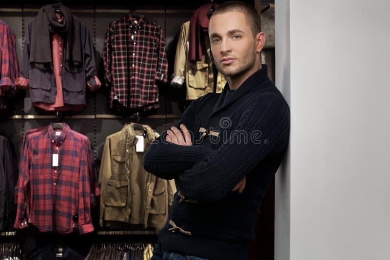 Młody człowiek wybiera odzieżowego w sklepie zdjęcia royalty free