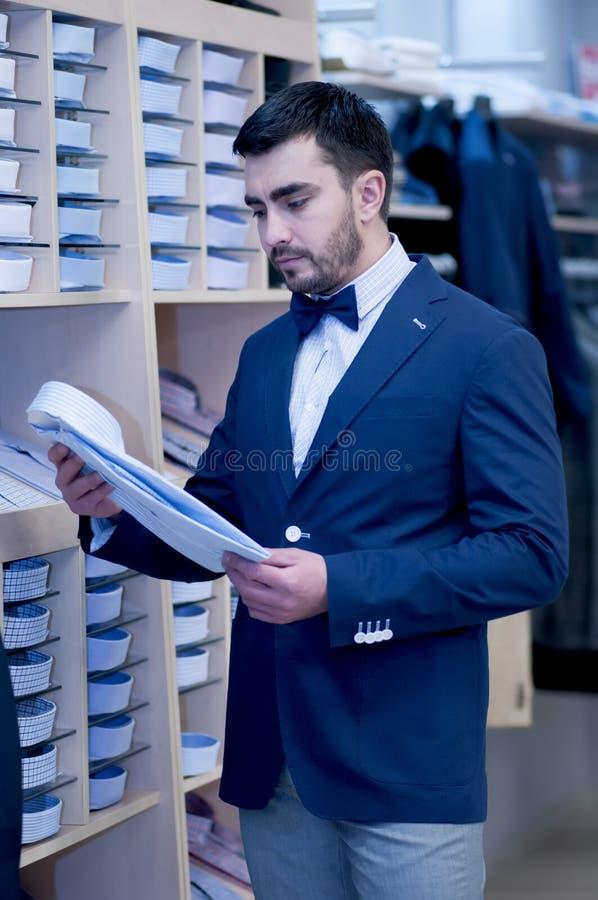 Młody człowiek wybiera trójnika - koszula przy sklepem zdjęcie stock