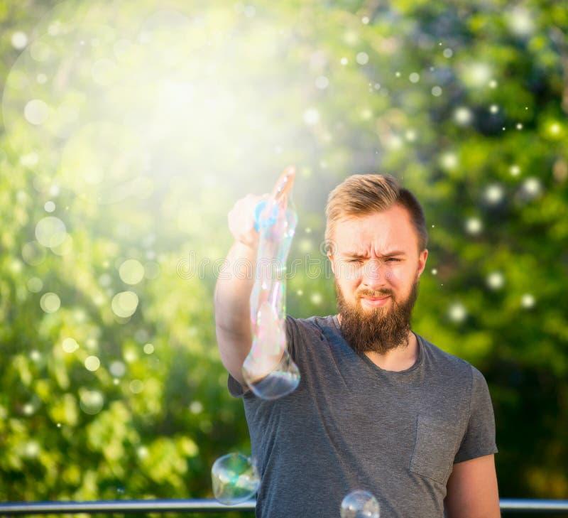 Młody człowiek wydaje czas w naturze z brodą, robi mydlanych bąbli natury tłu z bokeh obraz stock