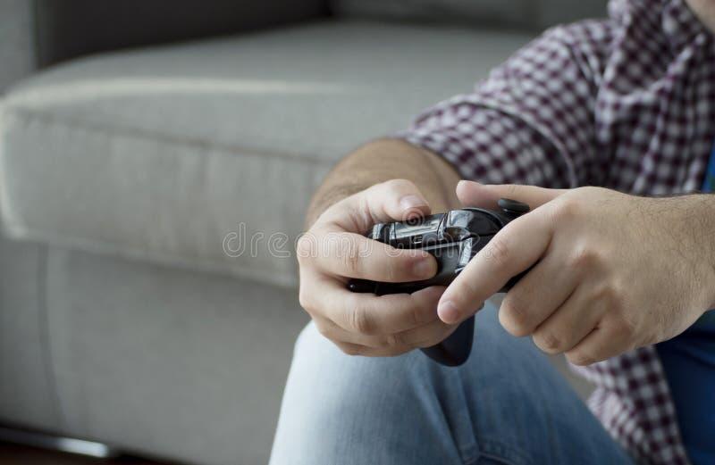 Młody człowiek wydaje t z joystickiem bawić się wideo gry w domu obraz stock