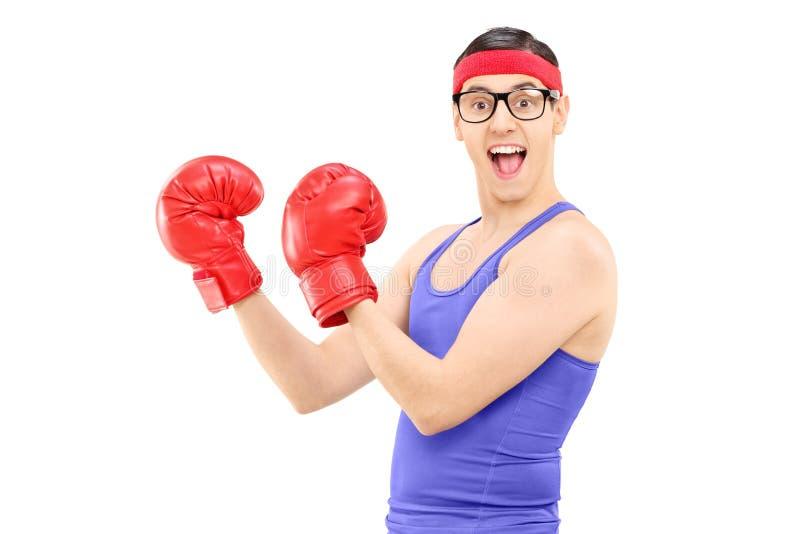 Młody człowiek z bokserskimi rękawiczkami pozuje dla kamery obraz royalty free