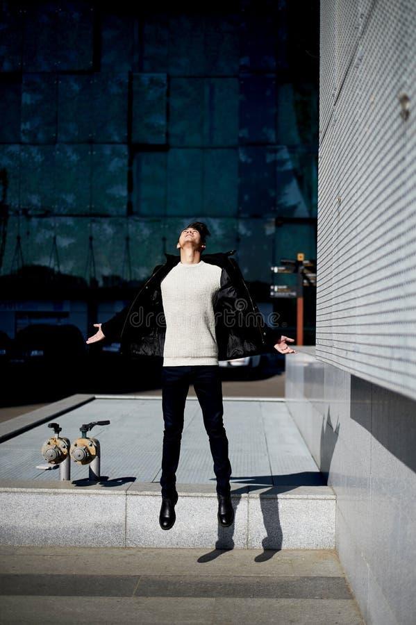 Młody człowiek z ciemnego włosy i oczu skakać Uczucie wolność lifestyle Wysoki wzrost fotografia royalty free