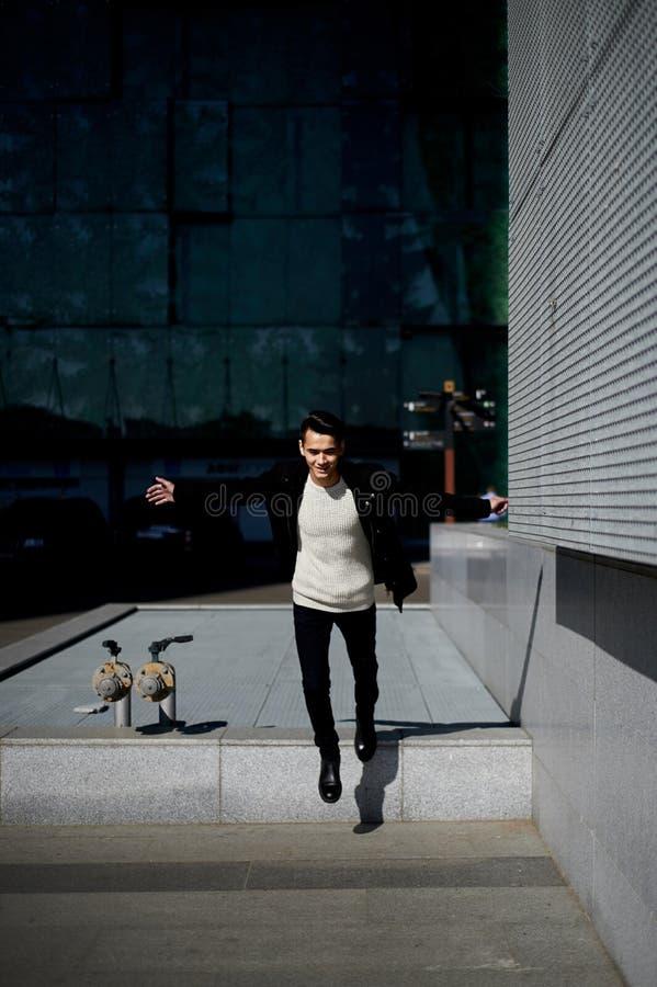 Młody człowiek z ciemnego włosy i oczu skakać Uczucie wolność lifestyle Wysoki wzrost fotografia stock