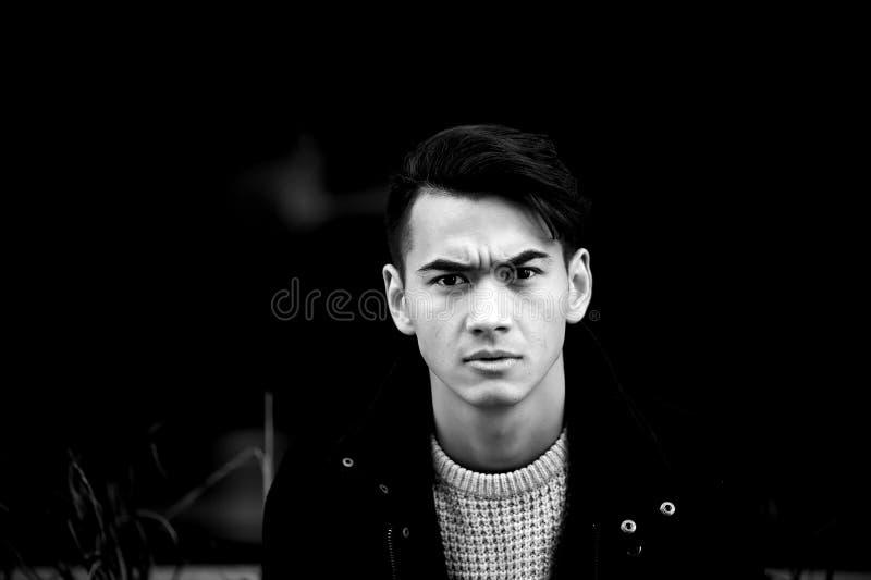 Młody człowiek z ciemnym włosy i oczami marszczy brwi zaduma frowns Wzorcowy pozować, emocje fotografia stock