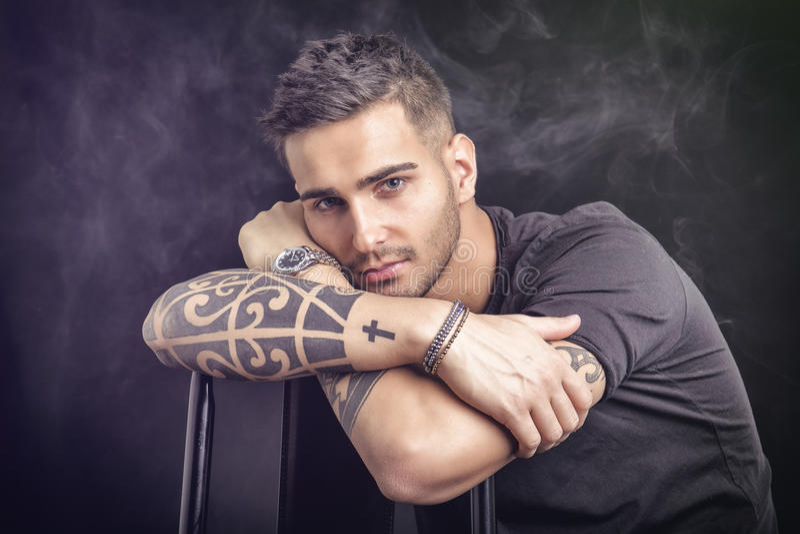 Młody człowiek z czarnymi tatuażami i koszulką fotografia royalty free