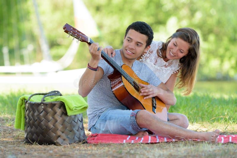 Młody człowiek z dziewczyny obsiadaniem na pyknicznej powszechnej bawić się gitarze fotografia stock