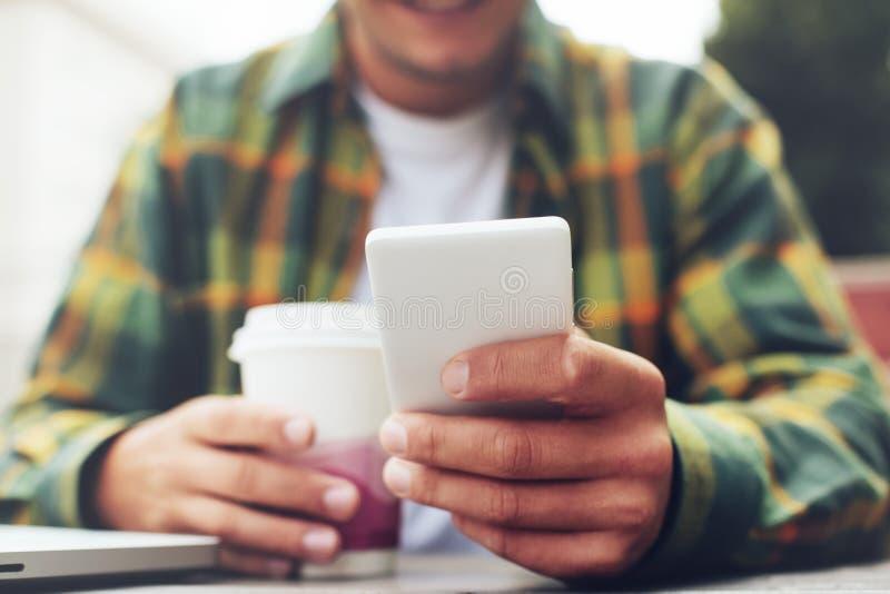 Młody człowiek z filiżanki kawy i smartphone pozyci wiadomości karmą, siedzi w ulicznej kawiarni zdjęcie royalty free