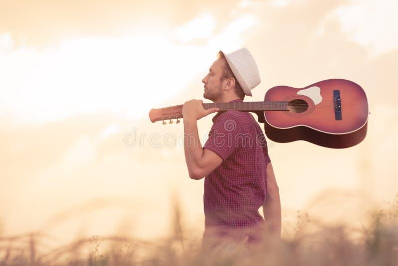Młody człowiek z gitarą akustyczną outdoors obrazy royalty free